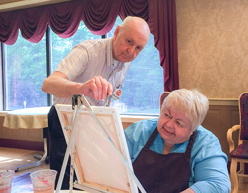 A volunteer assists a resident with her painting